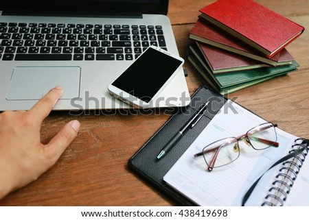 hand use phone and laptop on wooden table, layout laptop on working space, Internet of things lifestyle with wireless communication and internet with smart phone. - stock photo