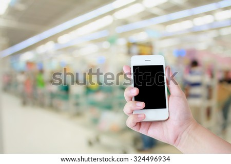 Hand use smartphone with Supermarket store background ,Cashier counter with customer - stock photo
