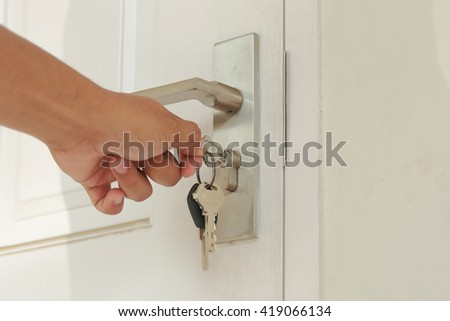 Hand use the key for unlocking and open the white door - stock photo