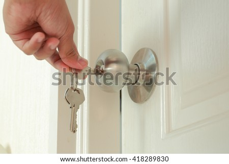 Hand use the key for unlocking the white door - stock photo
