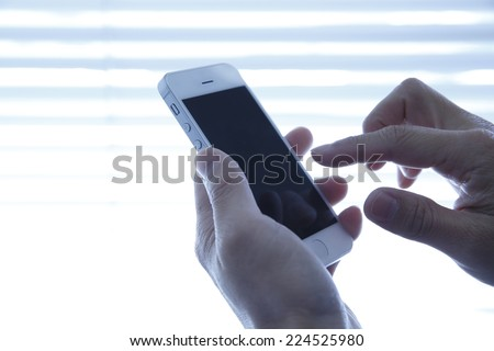 Hand using a Smartphone - stock photo