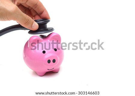 hand using a stethoscope with pink piggy bank