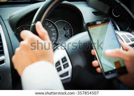 Hand using Cellphone while driving car,Businessman,parking