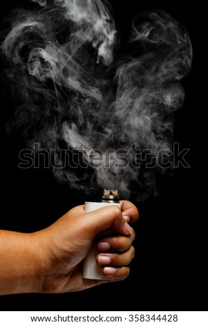 Hand using e-cigarette/e-cig/vape. And releasing a smoke from a rebuildable drip atomizer (RDA) over dark color background, close up