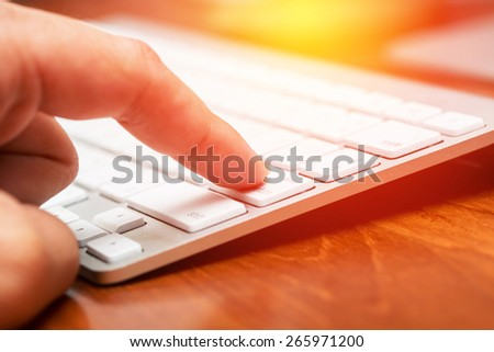 Hand using keyboard in office work place. Vintage filter. - stock photo