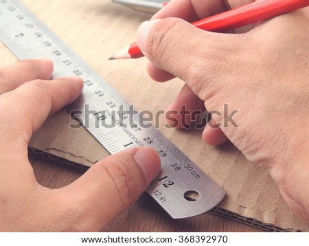 Hand using pencil and ruler on wood table