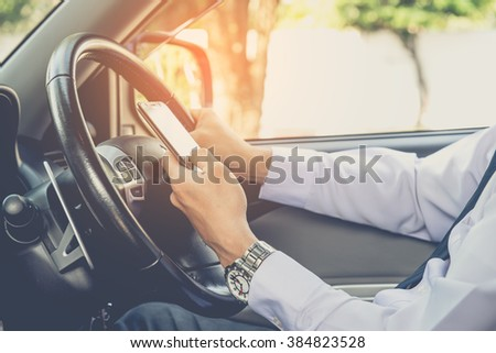 Hand using phone sending a text while driving to work ,businessman ,vintage color tone - stock photo