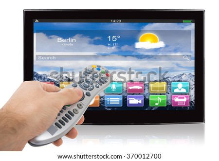 Hand using remote control of smart flat screen television against white background