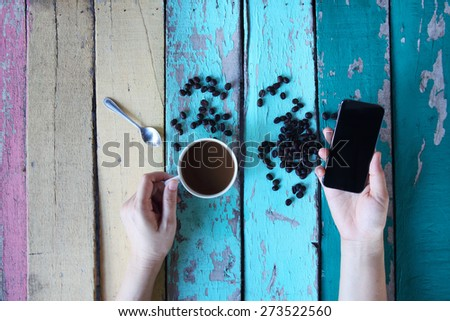 hand using smart phone in coffee shop - stock photo