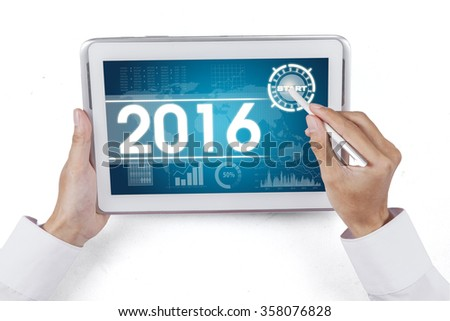 Hand using stylus pen for touching digital tablet with the economic forecast for 2016 - stock photo