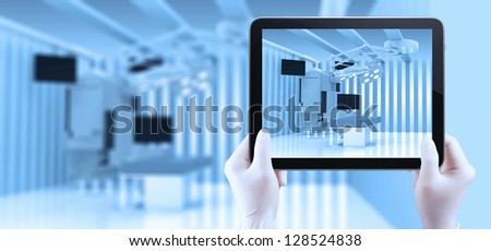 hand using tablet computer show equipment and medical devices in modern operating room - stock photo