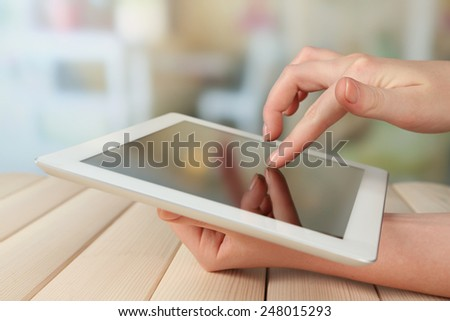 Hand using tablet PC on wooden table and light blurred background