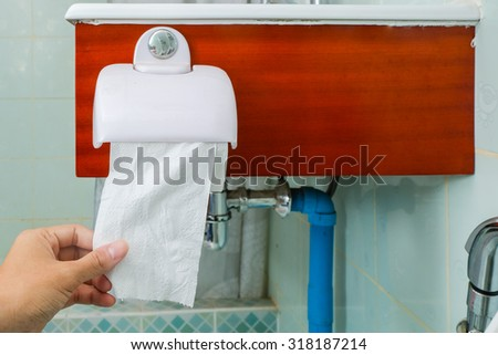 Hand using toilet paper / Man hand holding the roll of toilet paper - stock photo