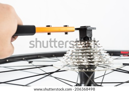 hand using tools to install bicycle rear crank set - stock photo