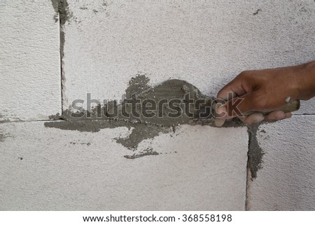 hand using trowel with wet concrete to plastering lightweight Concrete block, Foamed concrete block, raw material for industrial wall or house wall - stock photo
