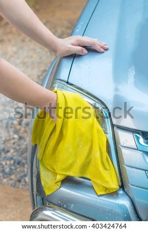 Hand washing car headlights with yellow cloth. - stock photo