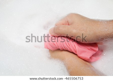 Hand washing clothes with bubble on white basin.