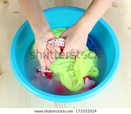 Hand washing in plastic bowl on wooden table close-up - stock photo