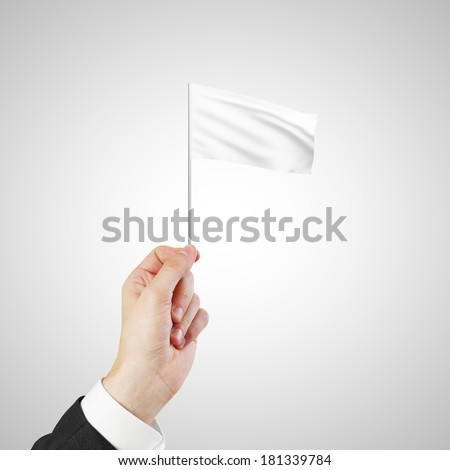 Hand waving a white flag isolated on black background - stock photo