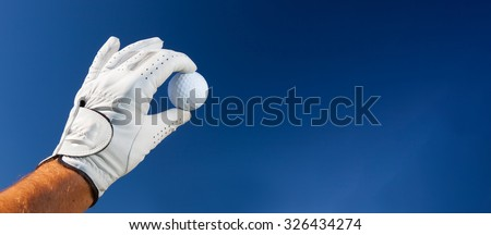 Hand wearing golf glove holding a white golf ball over a deep blue sky. Large copy-space at the right for title and text. - stock photo