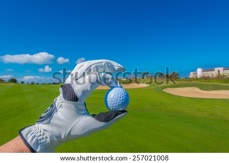 Hand wearing golf glove holding golf ball over beautiful golf course with blue sky. - stock photo