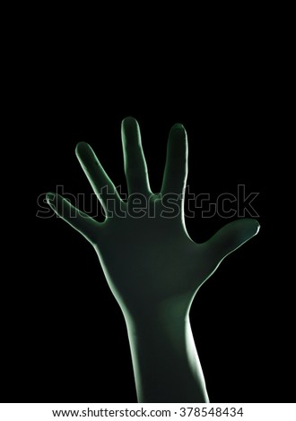 Hand Wearing Protective or Surgical Gloves on a Black Background - stock photo