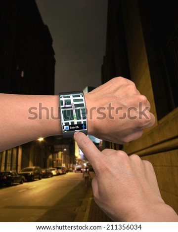 hand wearing wrist watch with GPS on street background - stock photo
