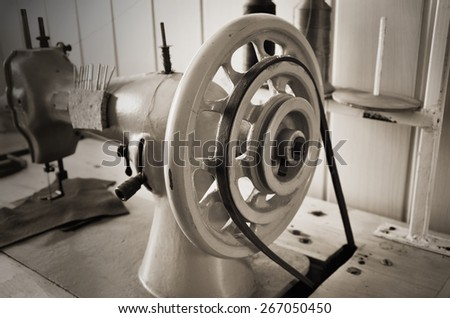 hand wheel old sewing machine. close up, horizontal format, sepia, monochrome - stock photo
