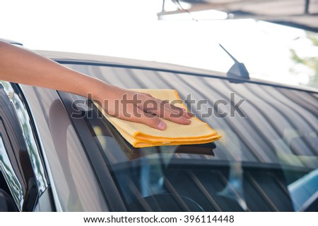 Hand wipe cleaning the car glass front with yellow microfiber cloth  - stock photo