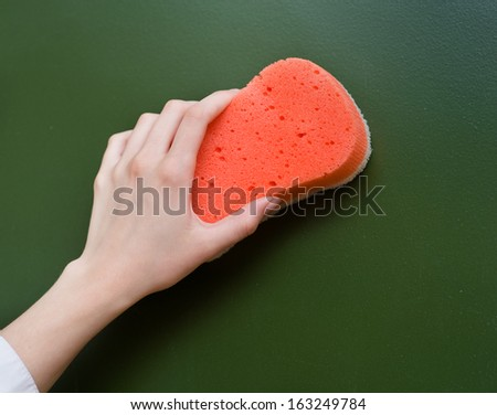 hand wipes the chalkboard, with a sponge - stock photo