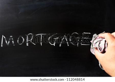 Hand wiping off mortgage on blackboard using rag - stock photo