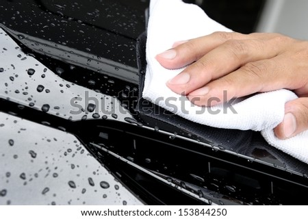 hand wiping water on black car - stock photo