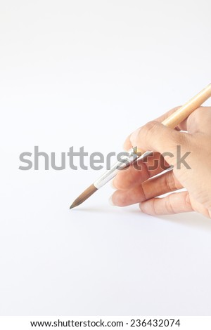 Hand with a brush. Over a grey empty paper, drawing imitation - stock photo