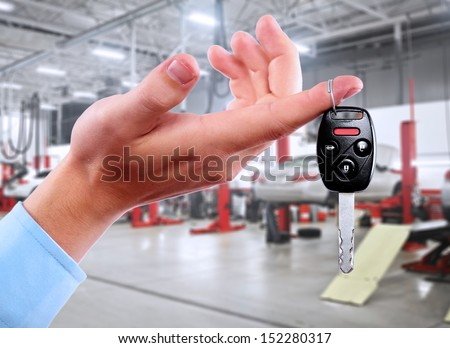 Hand with a car keys in auto repair service.