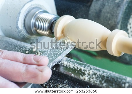 hand with a chisel in the course of the woodwork on the machine - stock photo