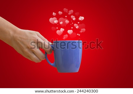 Hand with a cup. Cup of coffee with steam in heart shape