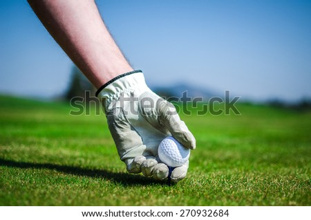 Hand with a glove is placing a tee with golf ball in the ground. Golf course with green grass with mountains in the background. Soft focus or shallow depth of field. - stock photo
