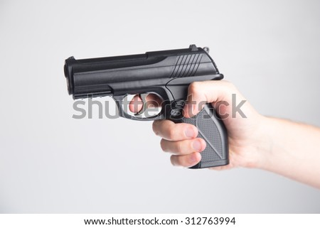Hand with a gun - defence concept - stock photo