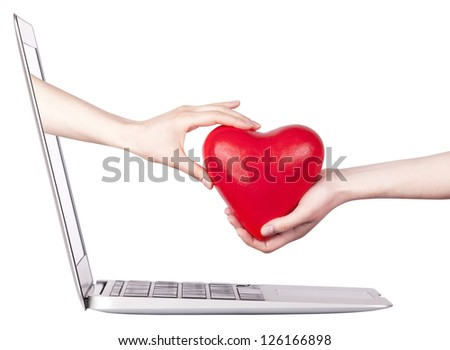 hand with a heart - gift come out from a screen of a laptop computer isolated on white background. - stock photo