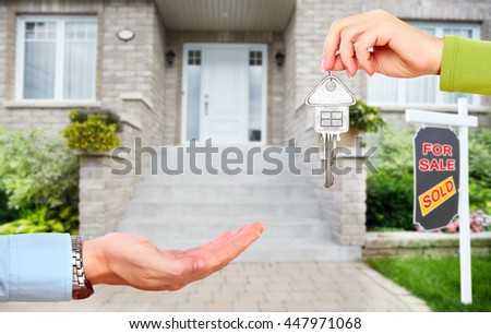 Hand with a key over new house background. - stock photo