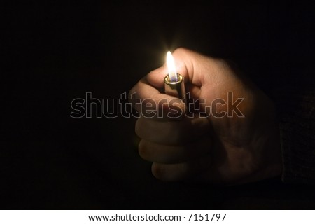 Hand with a lighter on a black background