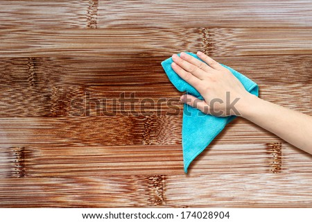 hand with a rag to dust the wood furniture - stock photo