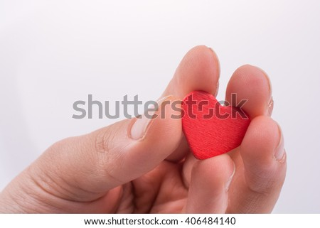 Hand with a red heart on a white background
