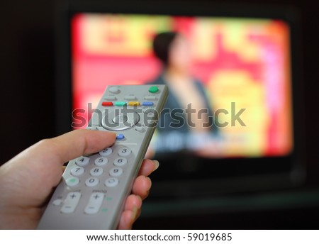 Hand with a remote control about to change TV channel - stock photo