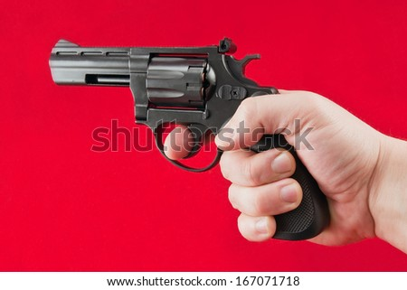 hand with a revolver on a red background - stock photo