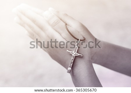 Hand with a rosary against gray background, religious concept.process in vintage color tone - stock photo
