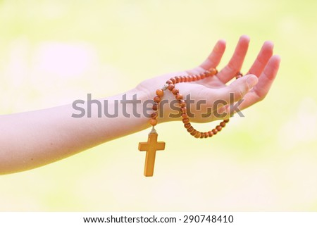 Hand with a rosary against green background - stock photo