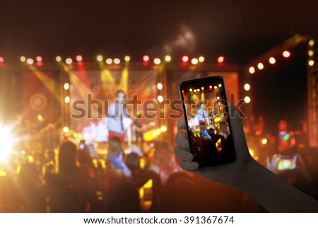 Hand with a smartphone records live music festival, live concert, live concert. - stock photo
