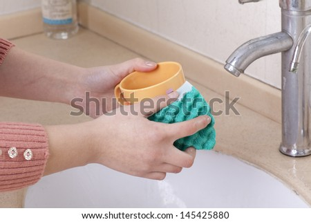 Hand with a sponge cleaning cups