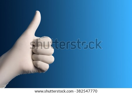 Hand with a white surgical glove showing the ok sign against a blue background